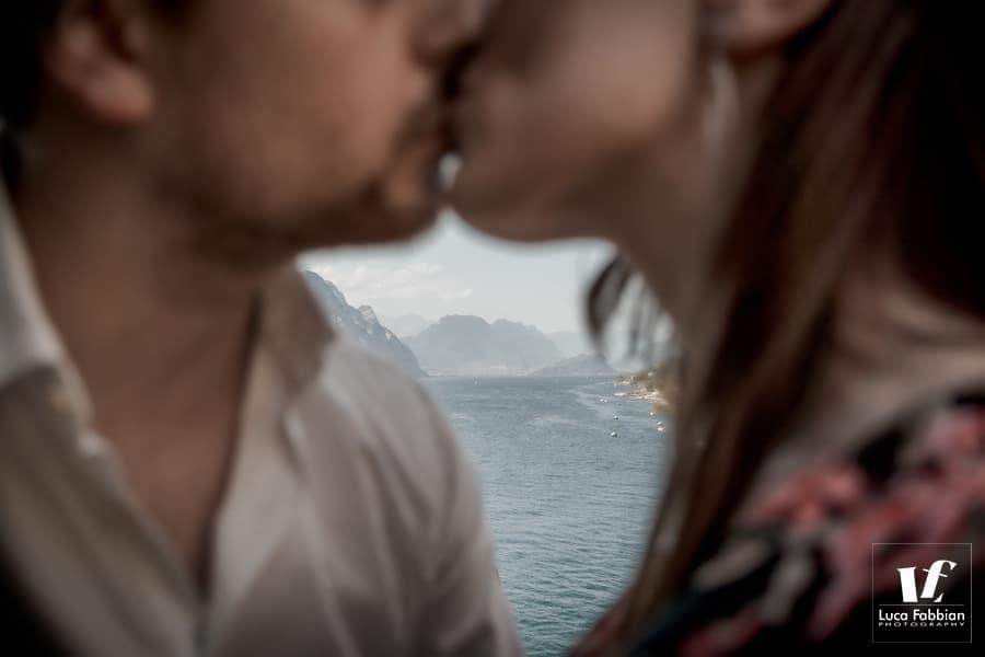 bacio tra fidanzati con sfondo del lago di Garda